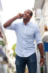 happy man walking on street talking on smart phone