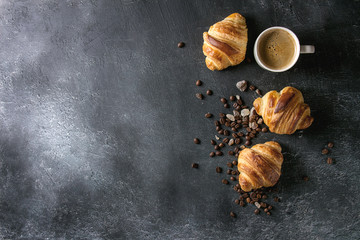 Fresh baked traditional croissants and mug of espresso coffee, coffee beans, sugar over black texture background. Top view, copy space