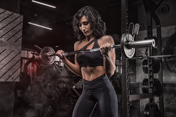 Young beautiful girl bodybuilder doing exercises in the gym using a barbell, exercises for the...