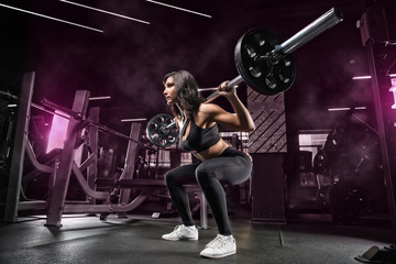 Young muscular girl weightlifter bodybuilder, personal trainer, makes a set of exercises for the development of leg muscles, squats with a bar, in the gym athletic hall.