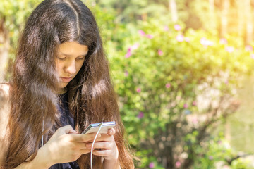 Young long haired girl using the phone in the city park on a summer sunny day. Walking in summer park on the summer day. Portrait female  teenager with copy space.