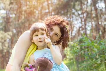 Young mother and little daughter playing in the park on a summer sunny day