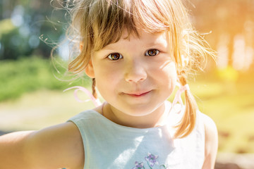Cute little girl plaing in the city park on a summer sunny day. Portrait little girl close up, big brown eyes. Toned photo.
