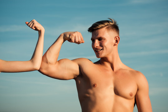 Man with strong hand biceps, triceps smile at female hand