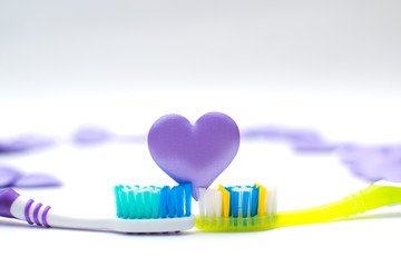 Toothbrushes on white background with purple hearts