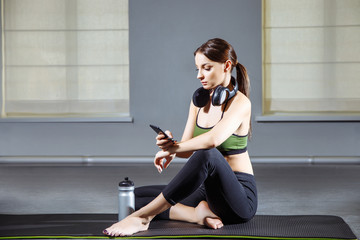 Fitness woman resting after workout in the gym