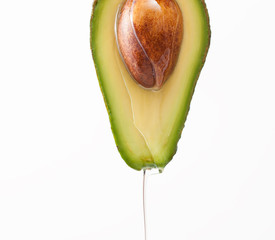 Dripping oil on a cut avocado on a white background