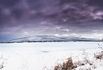 Winter landscape, frozen lake. Snow covered fields