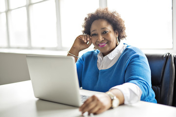 Portrait of cheerful business African-American working on laptop