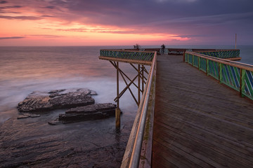 Sunrise over the Indian ocean from the wooden deck at the East London aquarium in South Africa