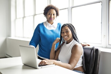 Mother And Teenage Daughter with Laptop Together