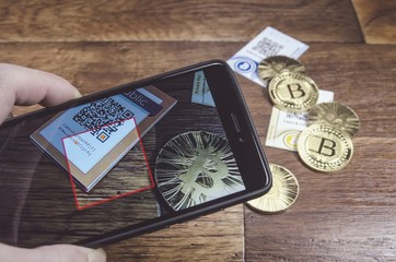 Modern way to pay anything with our smartphone and QR code reader with bitcoin virtual cryptocurrency