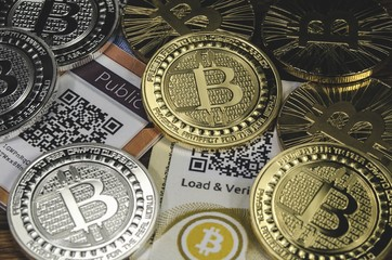 Bitcoin coins laying on paper wallet with QR code for contactless payment