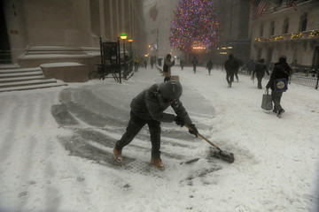 Man shovels snow along Wall Street during a snowstorm in New York City