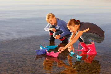 Two young girls floating paper boats on water
