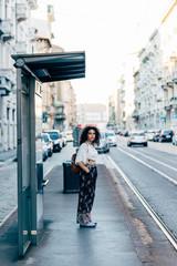 Woman standing at bus stop, Milan, Italy