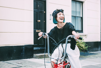Young stylish woman cycling retro bicycle on street