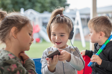 Young girl with friend, holding smartphone, wearing headphones