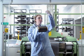 Female operator with bobbin of carbon fibre in carbon fibre production facility