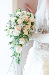 Bride is holding wedding bouquet in the registry office.
