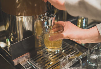 Woman pours a drink in the diner with self-service.