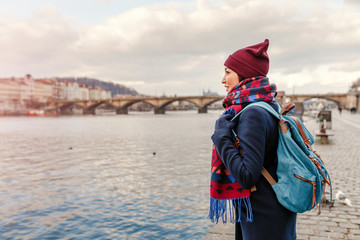 Young woman tourist in coat with backpack standing near bridge over the Vltava river in Prague