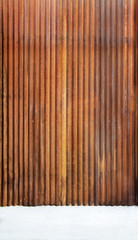 Corrugated zinc fence with old rusty surface brown with cement floor for the background.