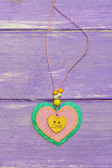 Valentines day jewelry. Valentines day felt heart jewelry isolated on a wooden background. Cute gift for mother. Top view