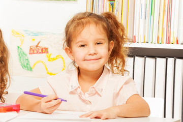 Clever girl with purple pencil sitting at the desk