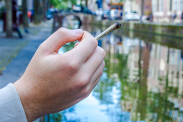 hand holding a cannabis joint on a canal in Amsterdam