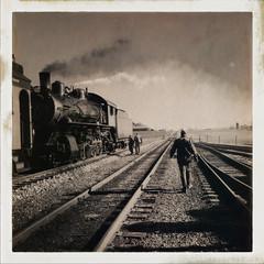 Men walking near old steam locomotive against sky