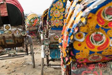 A ine of rickshaws parked on a roadside at Dhaka, Bangladesh