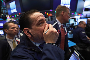 Traders wait for the Dow Jones Industrial Average to rise above 25,000 on the floor of the New York Stock Exchange shortly after the opening bell in New York