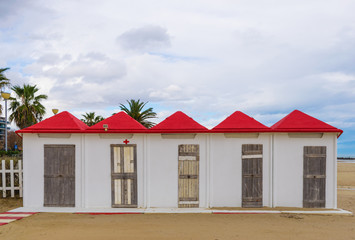 White beach cabins with red roofs