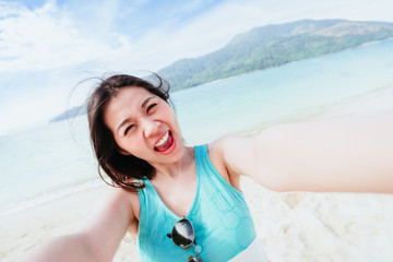 Happy pretty beautiful smiling Asian woman excited taking selfie on the beach in sunny day during vacation trip