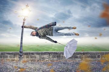 Mann wird von einem Unwetter weggeweht