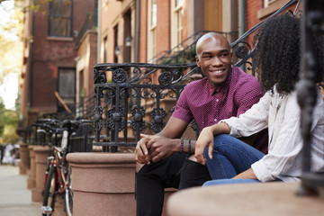 Couple Sit And Talk On Stoop Of Brownstone In New York City