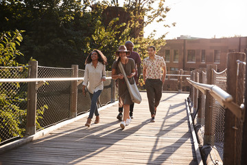 Group Of Friends Walking Along Bridge In Urban Setting