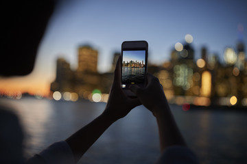 Silhouette Of Tourist Taking Photo Of Manhattan Skyline At Dusk