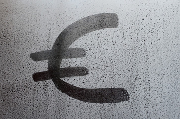 The euro currency symbol on the misted sweaty glass. Abstract background image. Euro currency concept