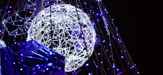 Fragment of the New Year tree. A lot of round lights of blue color are located on a conical frame