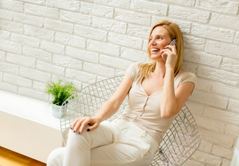 Blonde woman using mobile phone in the room