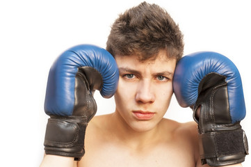 An angry young guy on a white background. Boxing gloves are on his hands. He is ready for a boxing fight