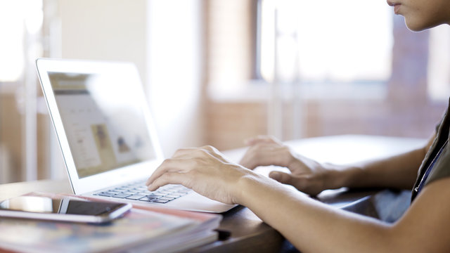 A young woman wearing a green shirt typing at her laptop in an office. Over the shoulder shot. Blurred laptop screen.