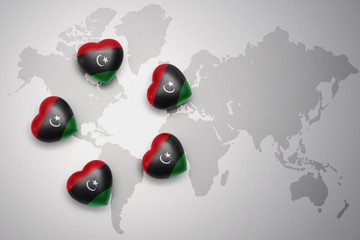 five hearts with national flag of libya on a world map background.