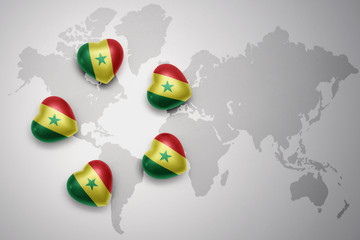 five hearts with national flag of senegal on a world map background.
