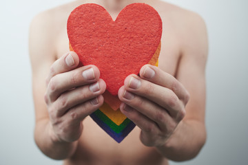 The LGBT community concept. Gay guy holds in his hands the hearts the colors of the rainbow