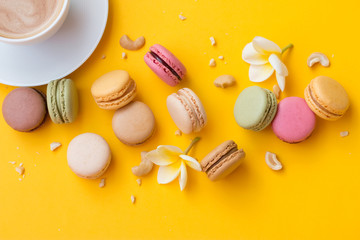 Makarons with cup of your favorite coffee, white flowers and pieces of nuts on yellow background.