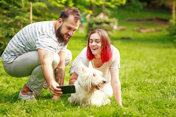 Bearded man and young woman with red hair making selfie with dog in park