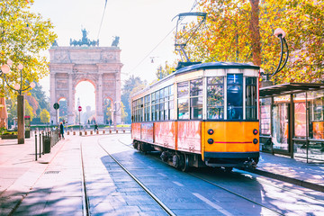 Acrylic Prints Milan Famous vintage tram in the centre of the Old Town of Milan in the sunny day, Lombardia, Italy. Arch of Peace, or Arco della Pace on the background.